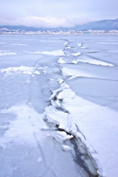 photo of snow-covered lake with heaving ice
