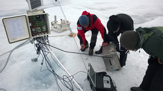 photo of three researchers working on ice monitoring equipment on a glacier
