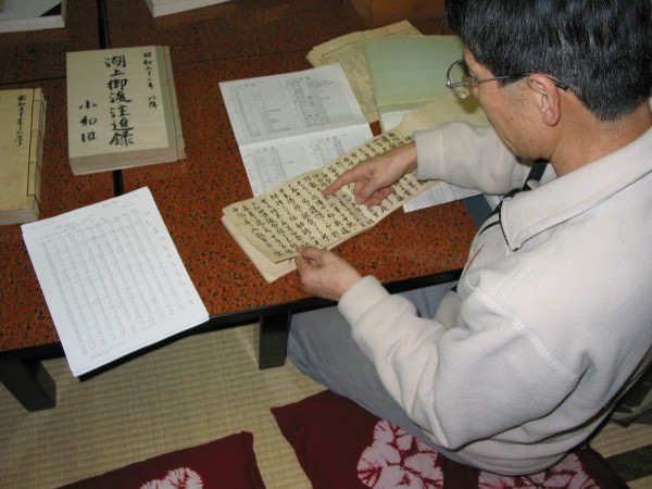 photo of a man pointing to records in a character-based script
