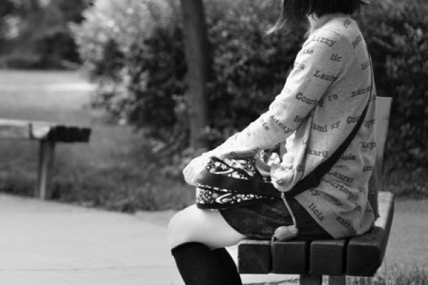 photo of student sitting on bench at keele campus