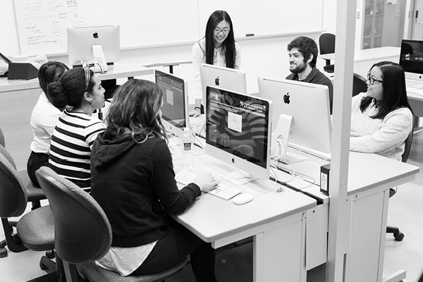 black and white photo of students facing each other while working on computers