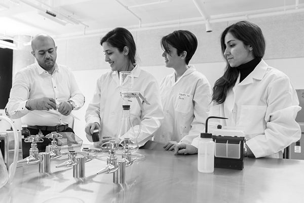 black and white photo of students working in a lab
