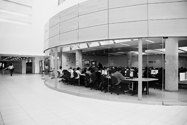 black and white photo of a computer lab behind a circular glass wall