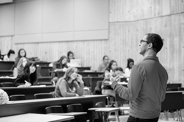black and white photo of an instructor addressing students inside a lecture hall