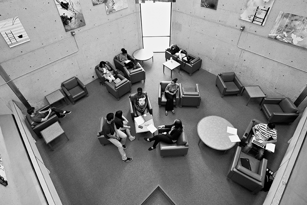 black and white overview photo of students studying in a library lounge