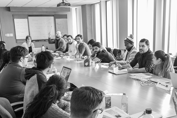 black and white photo of a large group of people having a discussion at a long table