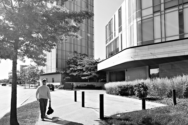 black and white photo of a man walking on a walkway in front of a building on a summer day