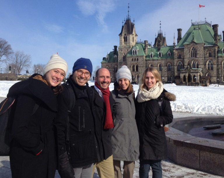 photo of five people on Parliament Hill with the West Block in the background