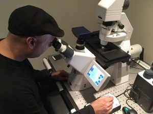 photo of Muhammad Yousaf looking into a microscope