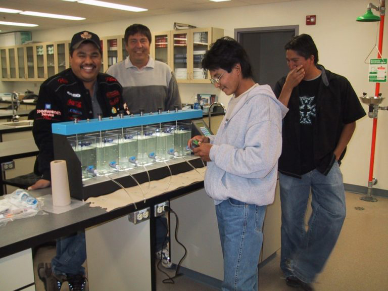 photo of four First Nations persons looking at water samples