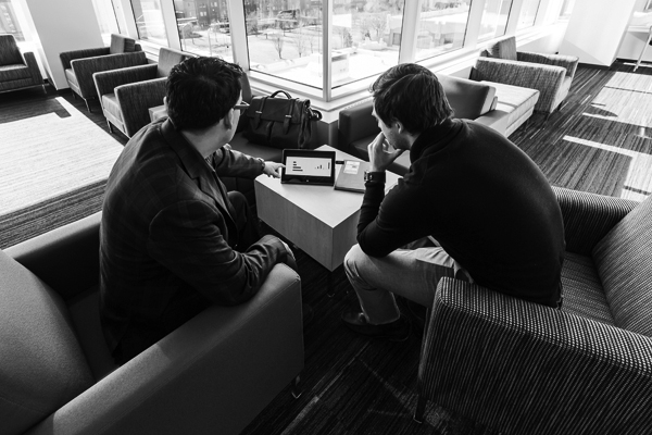 black and white photo of two people sitting in a lounge looking at a tablet