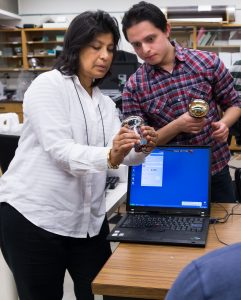 photo of Supervisor Sampa Bhadra, left, and Physics PhD student Elder Pinzon Guerra at work in the lab.