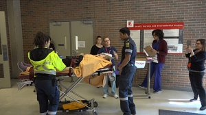 photo of emergency responders with a patient on a gurney