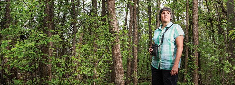photo of Bridget Stuchbury standing in a forest. She is holding binoculars