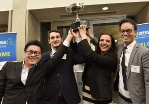 photo of four people raising a trophy over their head