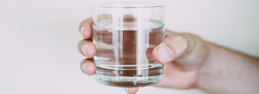 photo of a hand holding a glass half-filled with water