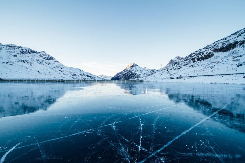 photo of a frozen lake with mountains in the background