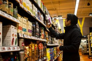 photo of Kam Phung examining a package of coffee in front of supermarket shelves