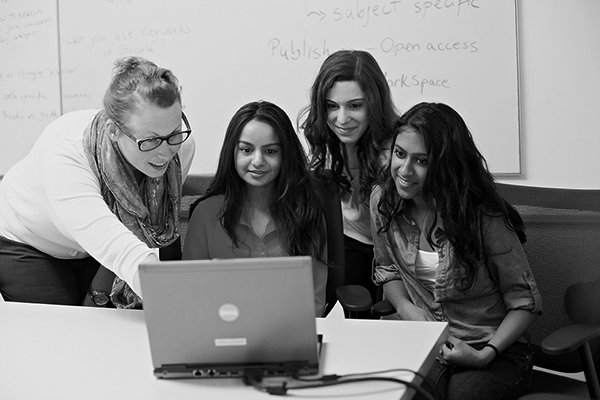 image of a group of students gathered around a laptop
