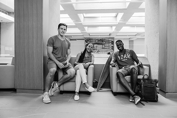 photo of three students lounging in a hallway