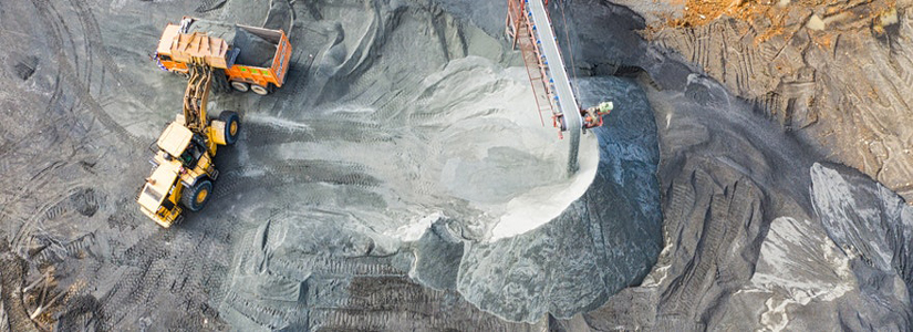 overhead photo of excavator filling a dump truck in a pit