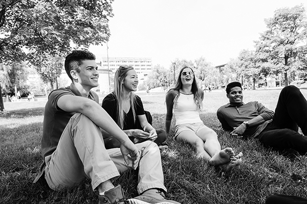 black and white photo of a group of students relaxing on the commons