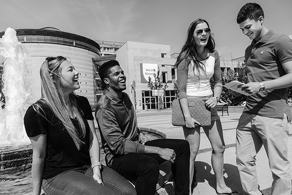 black and white photo of a group of students sitting at the Vari Hall fountain
