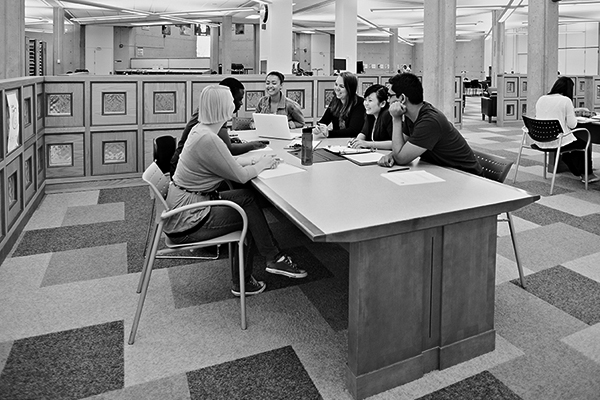 black and white photo of a group of students working at a library table