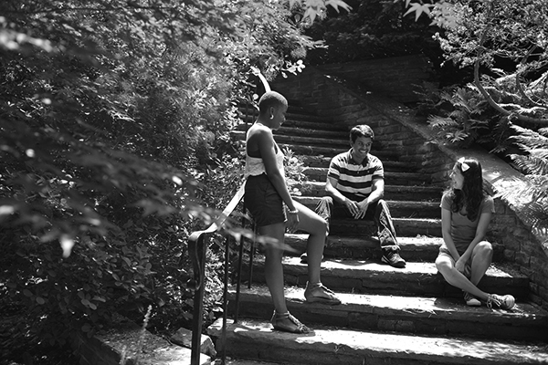 black and white photo of a group of students sitting on stone steps