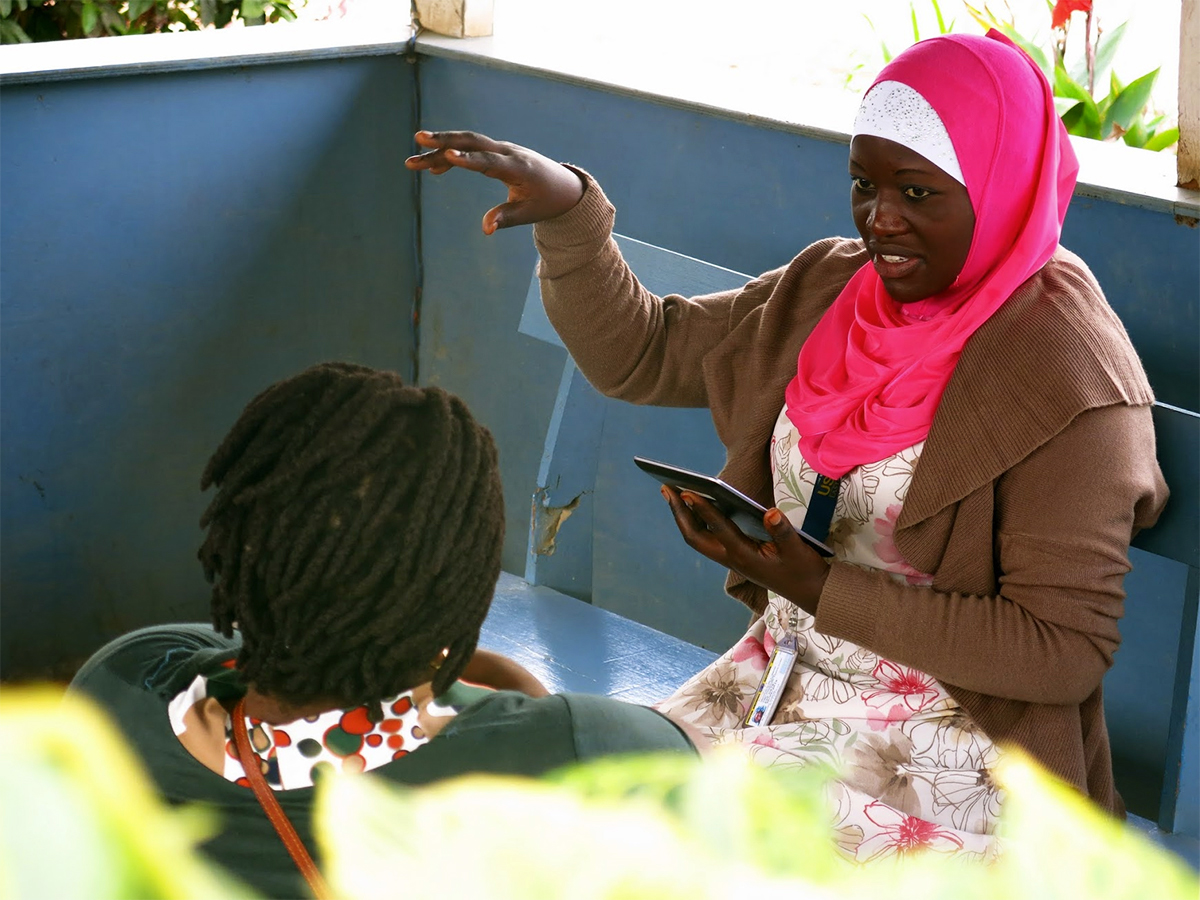 photo of a woman performing a needs assessment in a refugee camp