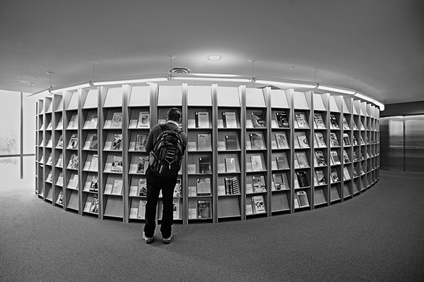 photo of a person looking at a library magazine rack