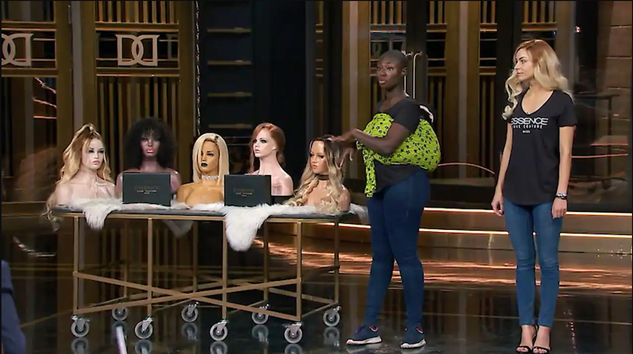 photo of Akosua Asare on the Dragon's Den stage with heads wearing wigs on a table