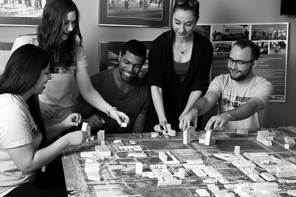 black and white photo of students locating blocks on a city plan